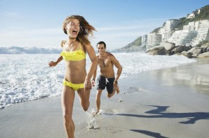 Man chasing happy woman on beach